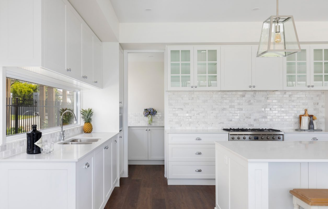 Open plan kitchen with brown wooden floor, butler's pantry, white Calacatta marble benchtops, freestanding stove and a window