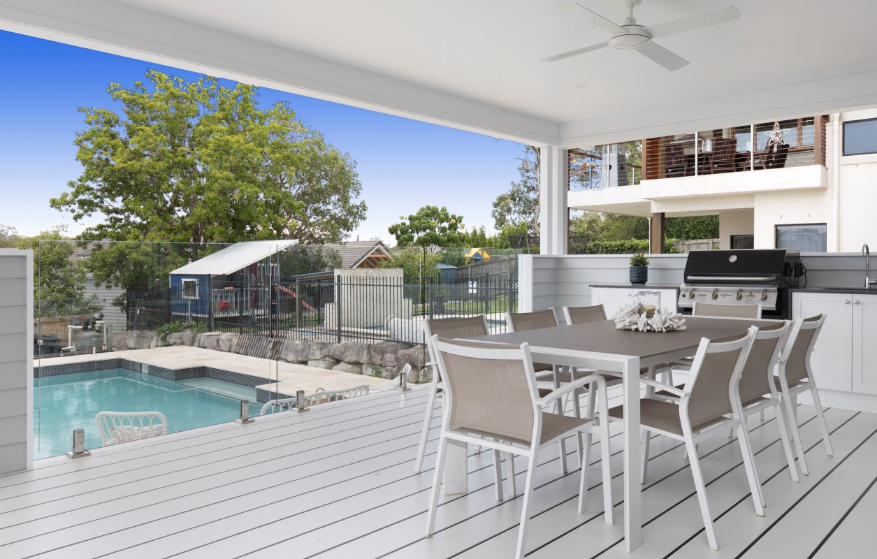 Deck with outdoor kitchen and dining table facing a backyard swimming pool in a white queenslander